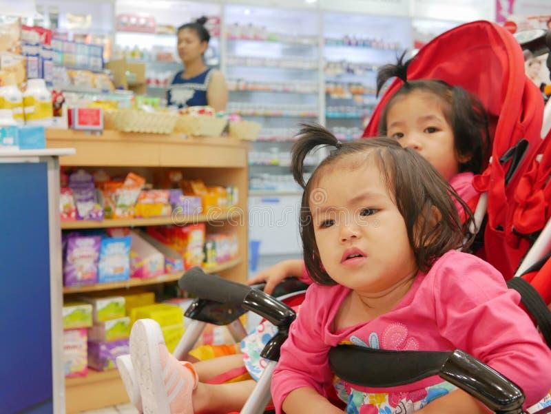 Małej Azjatyckiej dziewczynki frontowy dostawać zanudzający czekać na długiego czas w wózku spacerowym dla jej macierzystego kupi obraz royalty free
