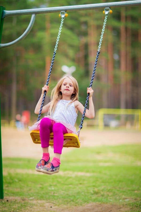 Małej blondynki dziewczyny uśmiechnięty chlanie outdoors na playgroung zdjęcie stock