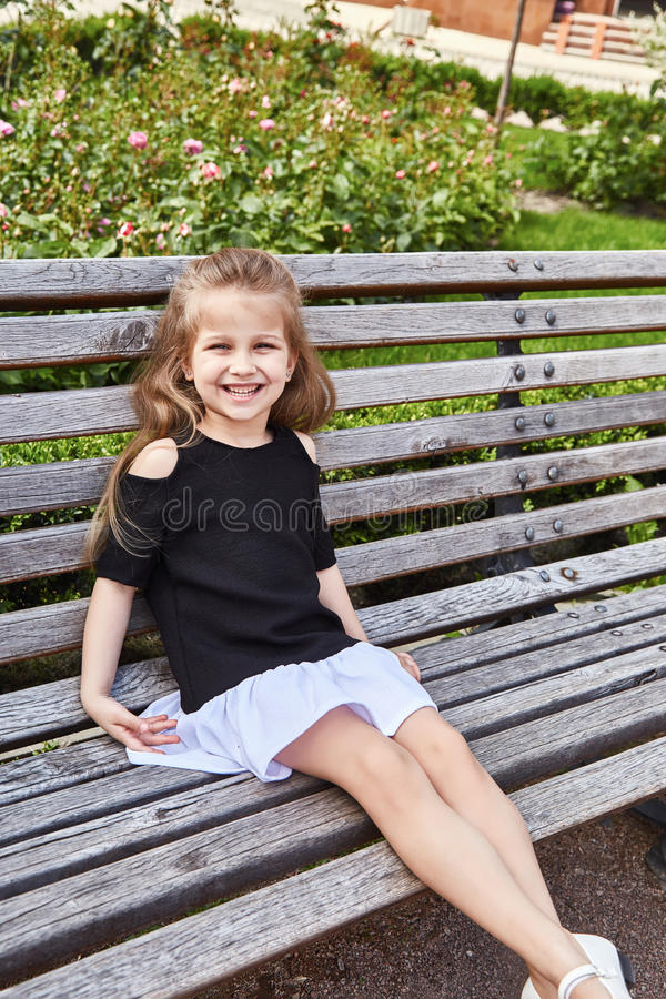 Małej dziewczynki ładnej twarzy dzieciaka piękny obsiadanie na ławce fotografia royalty free