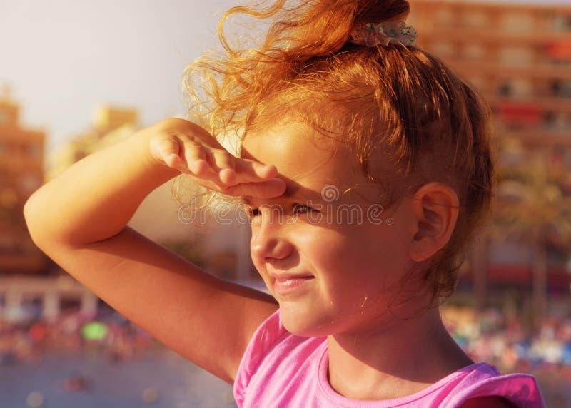 Małej dziewczynki ładni spojrzenia daleko zdala od dobra lewa strona ono uśmiecha się i mruży w świetle słonecznym na miasto plaż zdjęcie stock