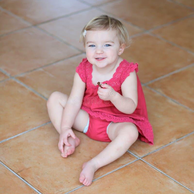 Małej dziewczynki łasowania ciastka siedzi na podłoga fotografia royalty free
