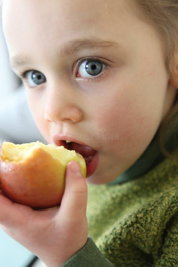 Małej dziewczynki łasowania jabłko fotografia royalty free