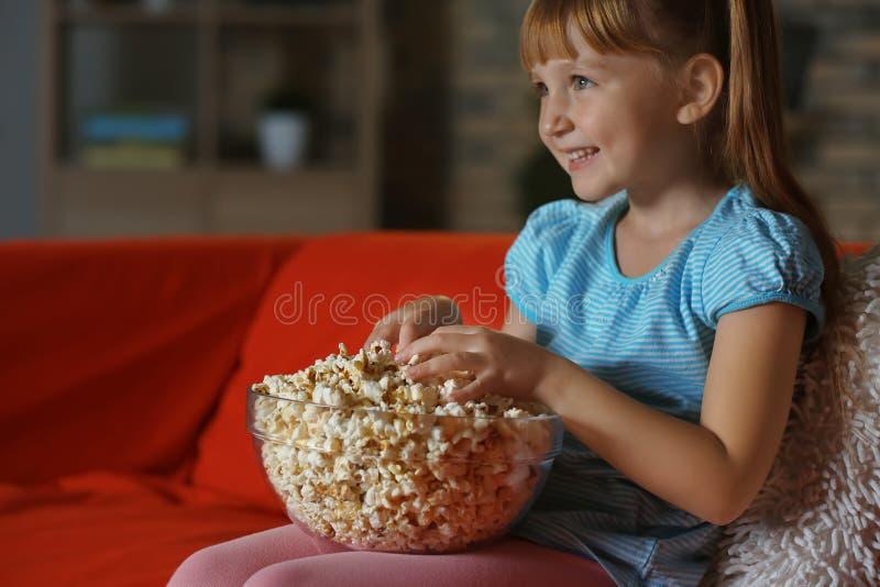 Małej dziewczynki łasowania popkorn podczas gdy oglądający TV na kanapie w wieczór zdjęcie royalty free