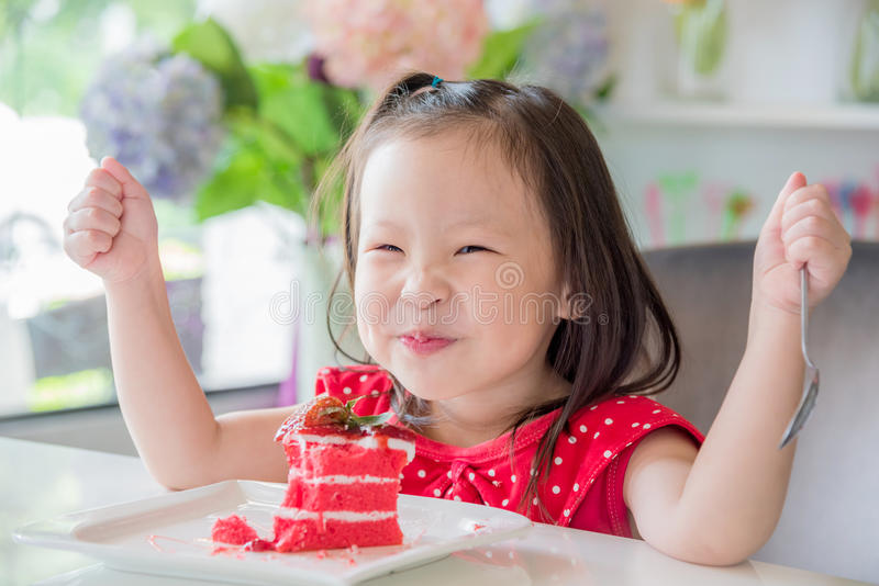 Małej dziewczynki łasowania truskawki tort obrazy stock