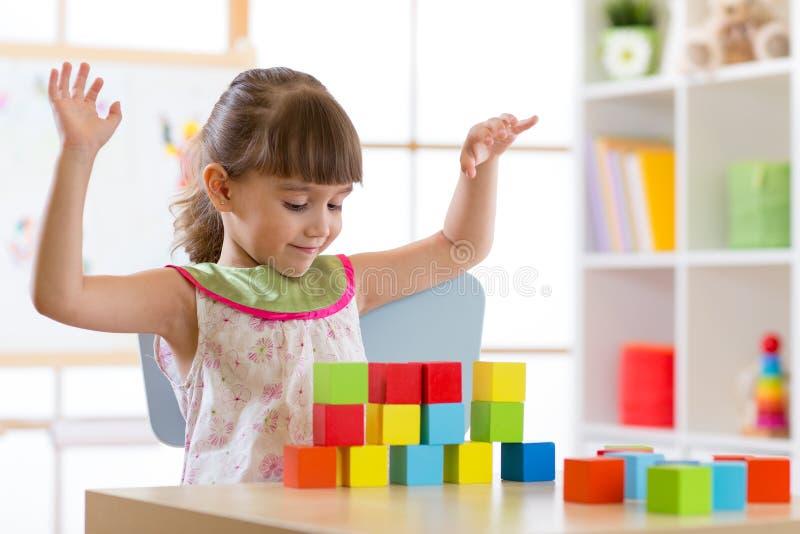 Małej dziewczynki budowy bloku zabawki lub daycare w domu Dzieciak bawić się z kolorów sześcianami Edukacyjne zabawki dla prescho zdjęcia stock