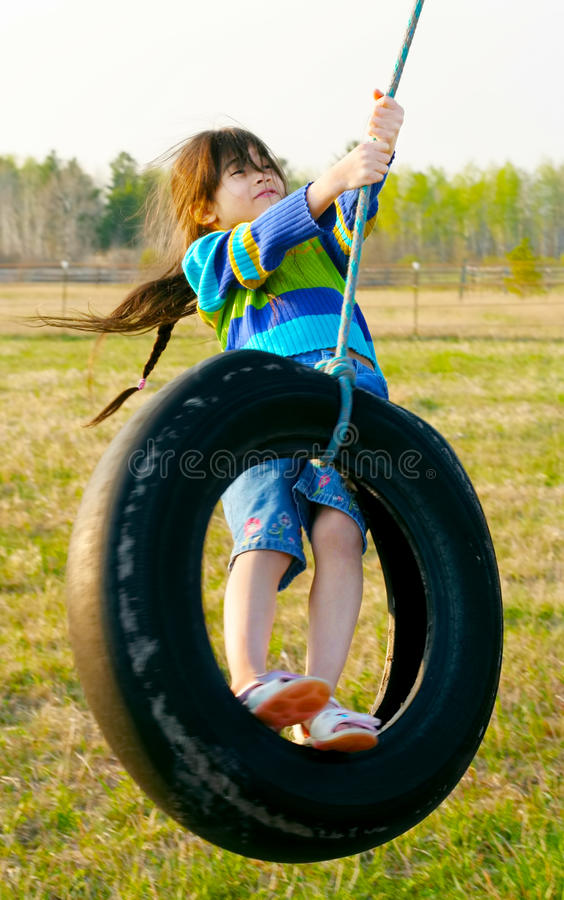 Małej dziewczynki chlanie na opony huśtawce fotografia royalty free