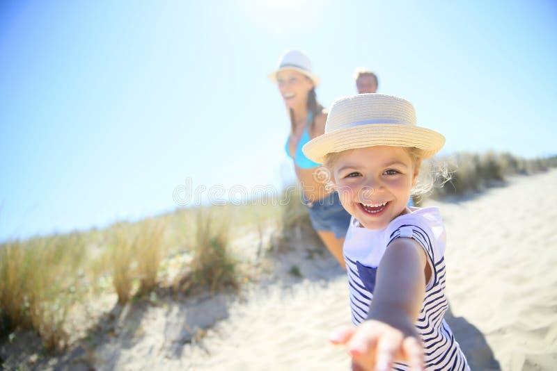 Małej dziewczynki ciągnięcia rodzica arn biega plaża zdjęcie stock