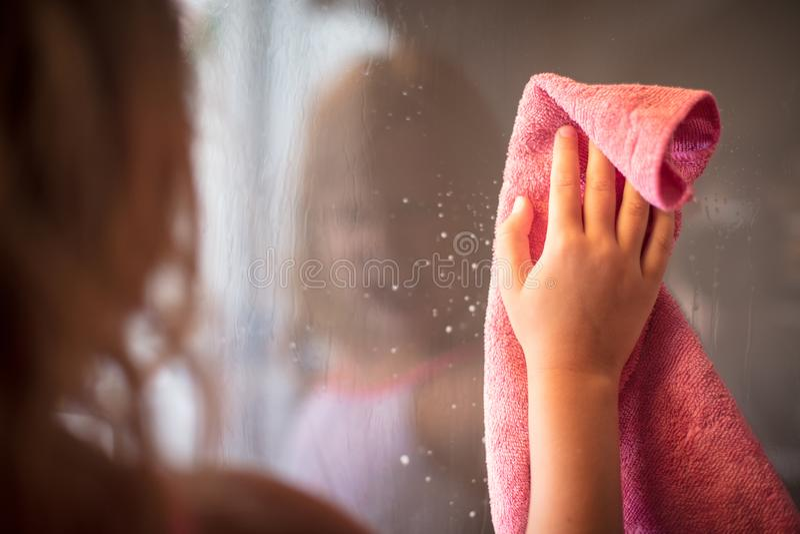 Małej dziewczynki cleaning okno fotografia stock