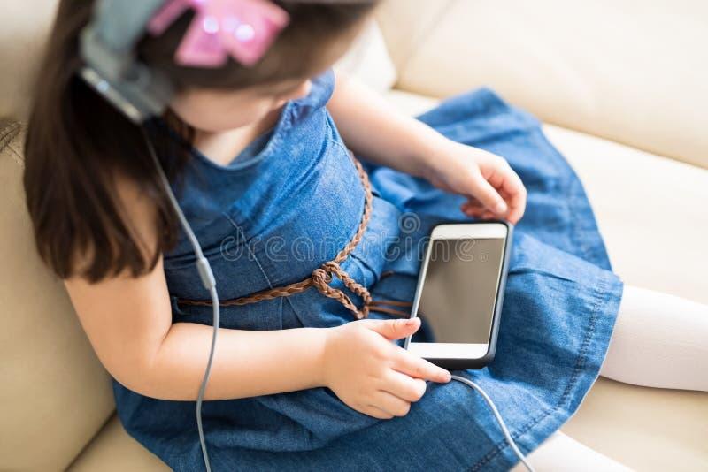 Małej dziewczynki dopatrywania kreskówki film na telefonie komórkowym zdjęcie royalty free