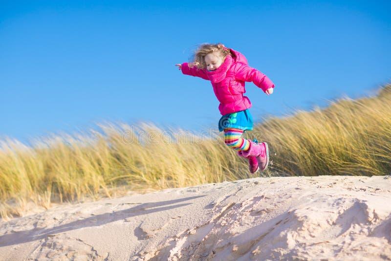 Małej dziewczynki doskakiwanie w piasek diunach obrazy royalty free