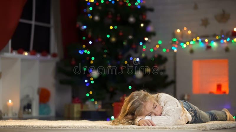 Małej dziewczynki dosypianie pod choinką, czekanie Santa, marzy teraźniejszość obrazy royalty free