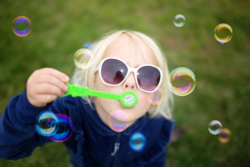 Małej Dziewczynki dziecka dmuchanie Gulgocze Outside na letnim dniu zdjęcie royalty free