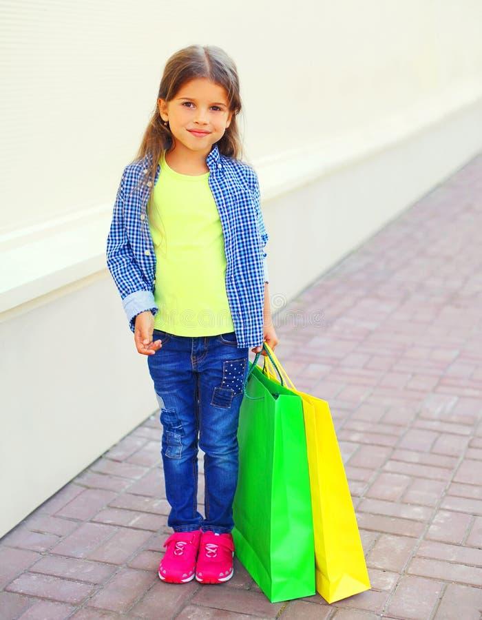 Małej dziewczynki dziecko trzyma torby na zakupy w mieście fotografia royalty free