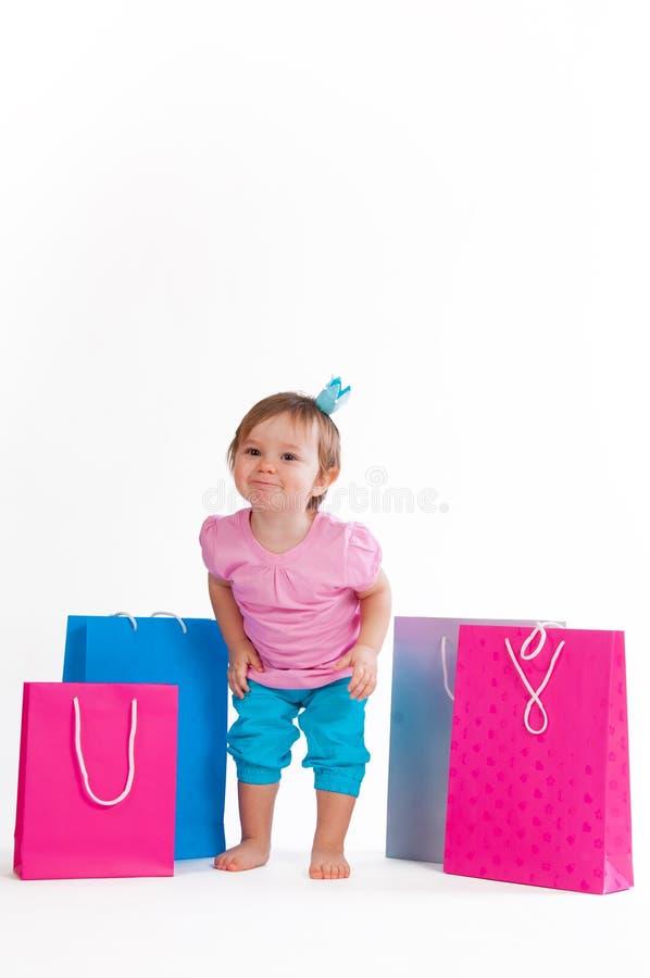 Małej dziewczynki Hamming stojaki z kolorowymi papierowymi torbami zdjęcia stock