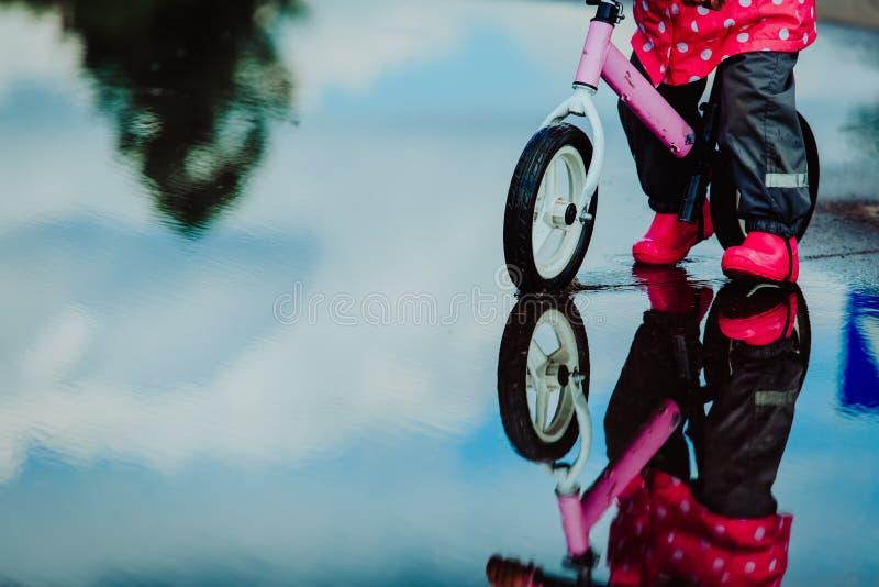 Małej dziewczynki jazdy rower w wodnej kałuży fotografia royalty free