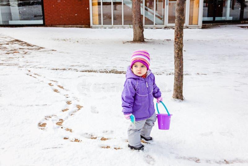 Małej dziewczynki jeden roczniak bawić się outside w zima parku, opuszcza ślada na śniegu C zdjęcie royalty free