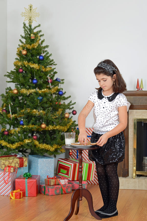 Małej dziewczynki kładzenia mleko ciastek mleko dla Santa zdjęcia royalty free