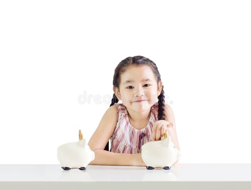 Małej dziewczynki kładzenia pieniądze na prosiątko banku Myśleć o oszczędzaniu fotografia royalty free