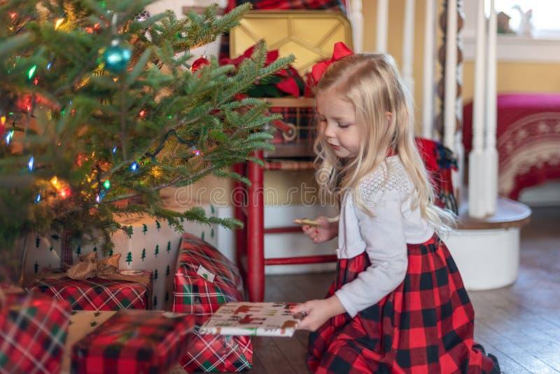 Małej dziewczynki klęczenie choinką patrzeje zawijających prezenty zdjęcia stock