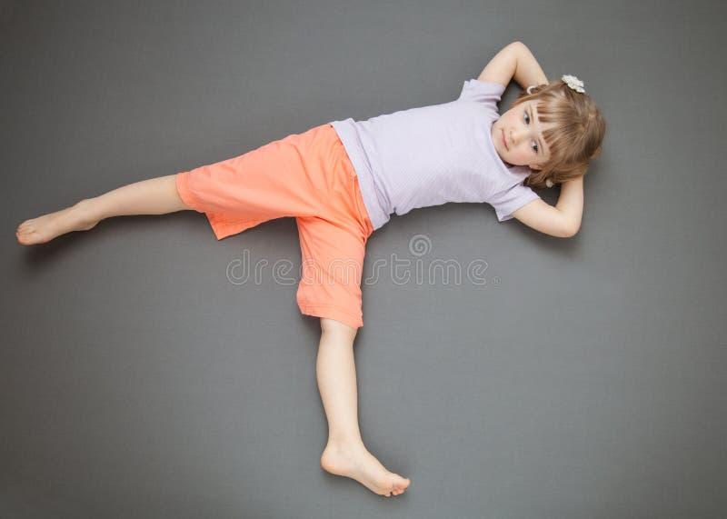 Małej dziewczynki lying on the beach na podłoga zdjęcie royalty free
