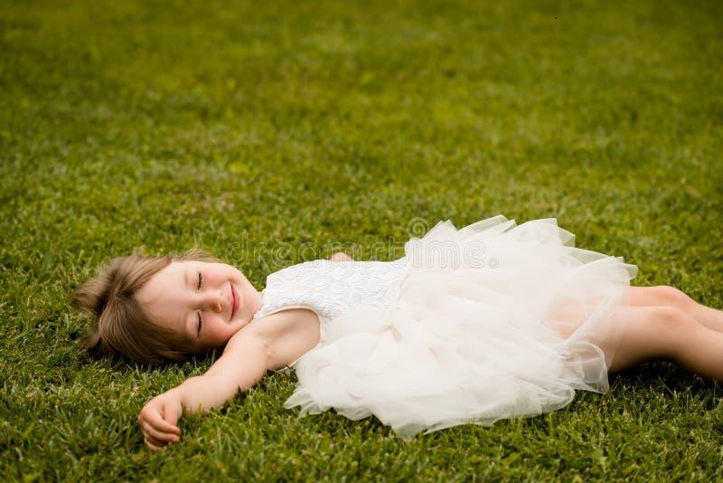 Małej dziewczynki lying on the beach na trawa gazonu ono uśmiecha się zdjęcie stock