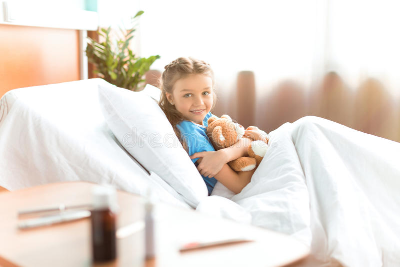 Małej dziewczynki lying on the beach w łóżku szpitalnym z misiem i ono uśmiecha się przy kamerą zdjęcia stock