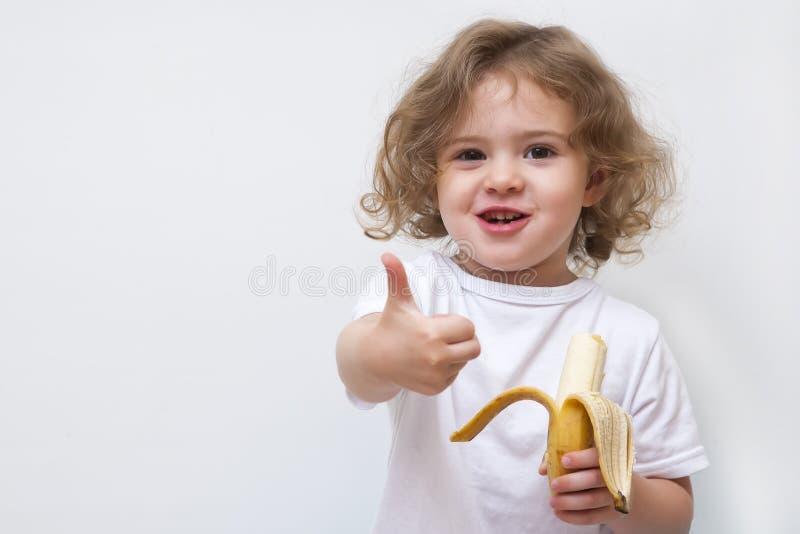 Małej dziewczynki mienia żółty banan i przedstawienie kciuk up zdjęcie royalty free