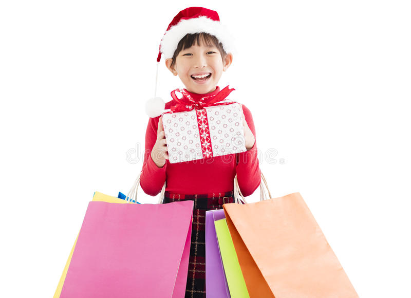 małej dziewczynki mienia Bożenarodzeniowi torba na zakupy i prezent obraz royalty free