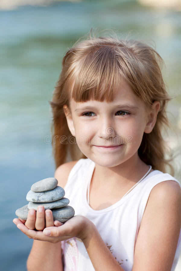 Małej dziewczynki mienia ostrosłup kamienie zdjęcie royalty free