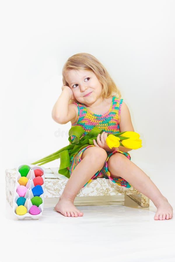 Małej dziewczynki mienia tulipany z Wielkanocnymi jajkami zdjęcia stock