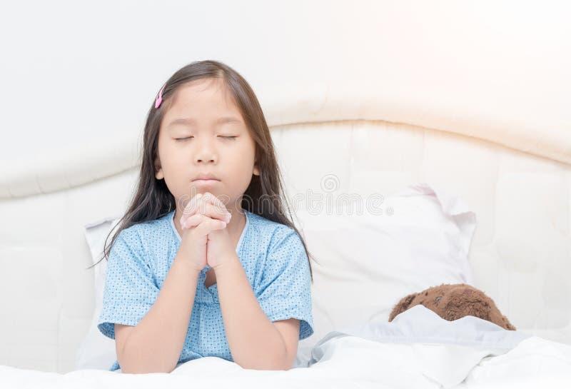 Małej dziewczynki modlenie na łóżku, duchowości i religii, zdjęcie royalty free