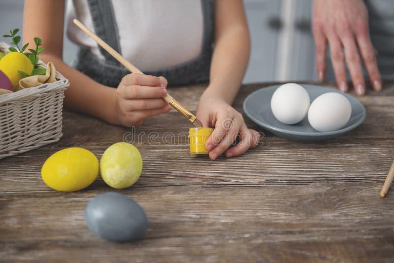 Małej dziewczynki narządzanie malować Easter jajka obraz stock
