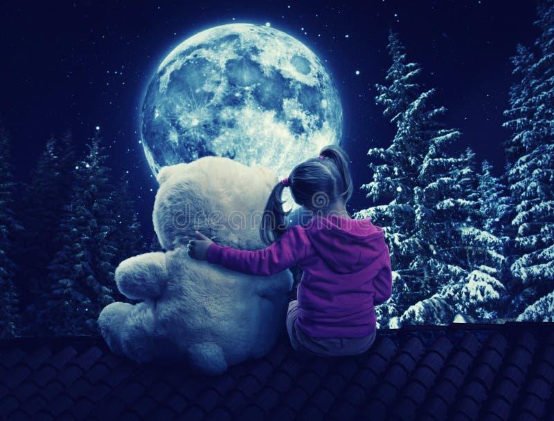 Małej dziewczynki obsiadanie na dachu z zabawka niedźwiedziem obraz royalty free