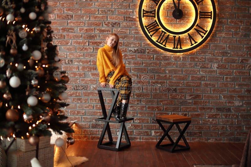 Małej dziewczynki obsiadanie na krześle blisko choinki zdjęcie stock