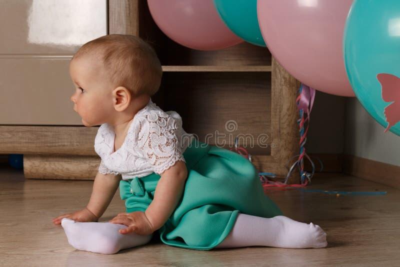 Małej dziewczynki obsiadanie na podłoga w pokoju obok balonów, pierwszy urodziny, świętuje jeden roczniaka błękitny i różowy piłk obrazy royalty free