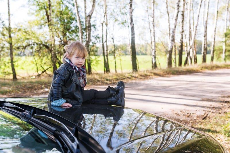 Małej dziewczynki obsiadanie na samochodowym cowl outdoors zdjęcie stock