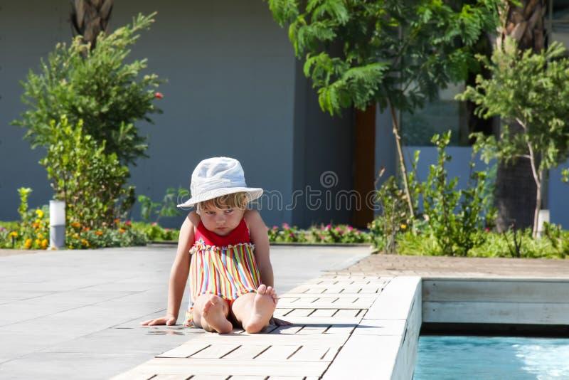 Małej dziewczynki obsiadanie obok basenu zdjęcie royalty free