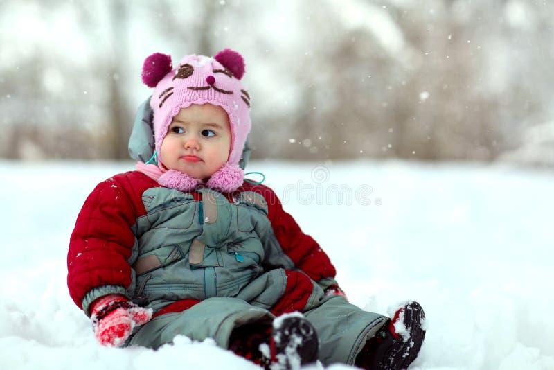 Małej dziewczynki obsiadanie w śniegu fotografia stock