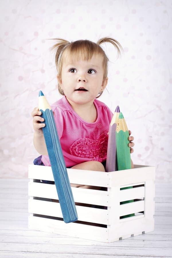 Małej dziewczynki obsiadanie w małym pudełku z dużymi kolorystyka ołówkami fotografia royalty free