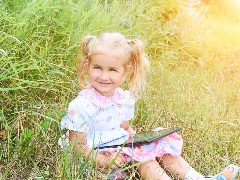 Małej dziewczynki obsiadanie w parku na słonecznym dniu i sztuka z pastylka komputerem osobistym obraz stock