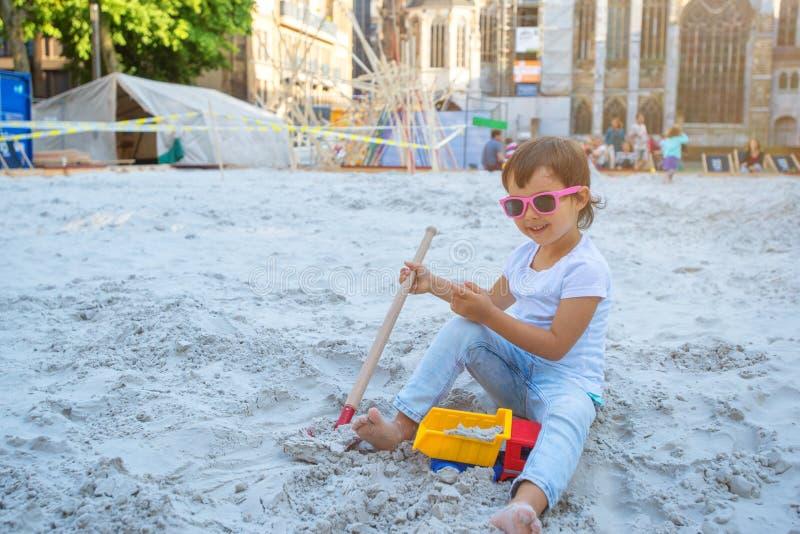 Małej dziewczynki obsiadanie w piaskownicie i bawić się z foremkami na boisku zdjęcie royalty free