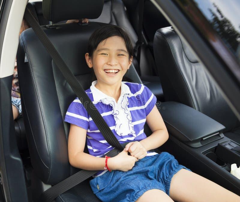 Małej dziewczynki obsiadanie w samochodzie z pasem bezpieczeństwa zdjęcia stock