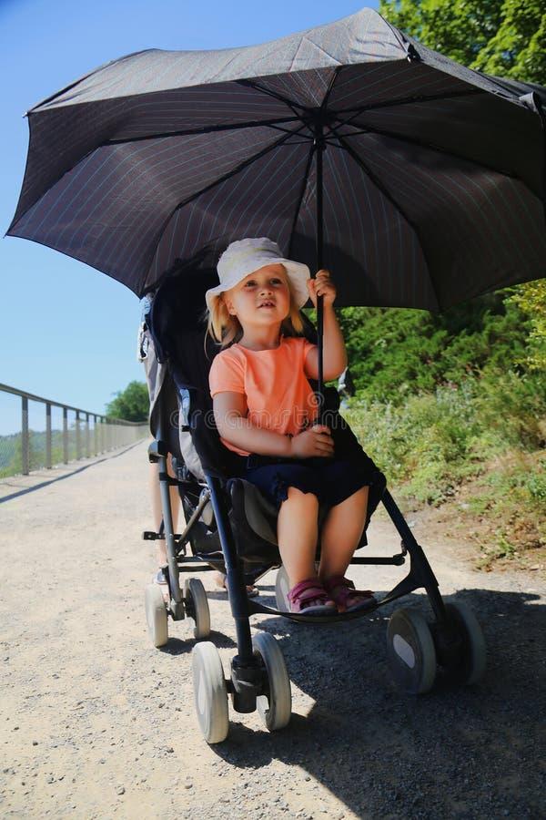 Małej dziewczynki obsiadanie w spacerowiczu Dziecko ochraniający od słońca dużym parasolem Dzieciaka Heatstroke zapobieganie na s obrazy royalty free