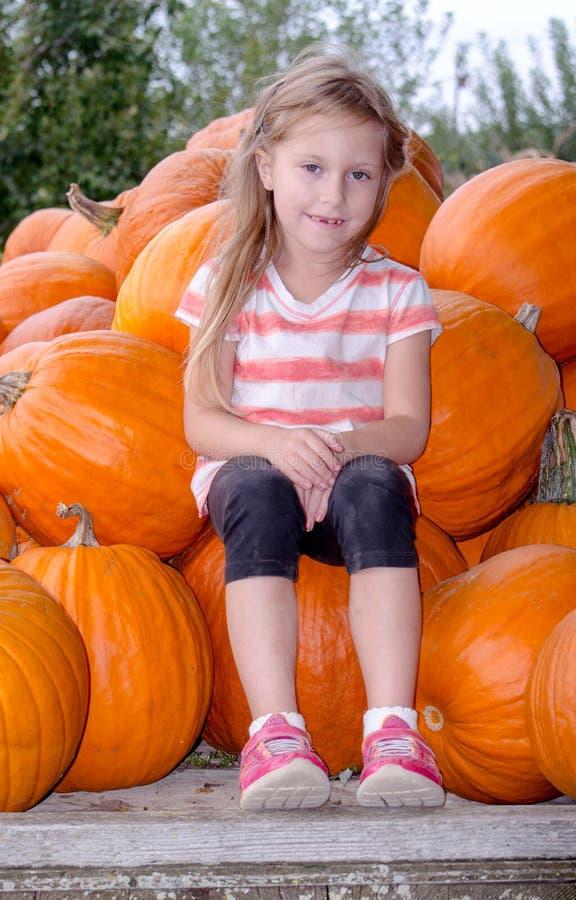 Małej dziewczynki obsiadanie z wielkimi baniami fotografia stock