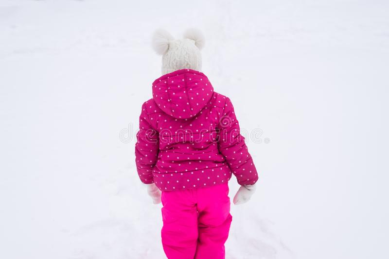 Małej dziewczynki odprowadzenie na śniegu, widzieć od behind bezpłatna przestrzeń obrazy stock