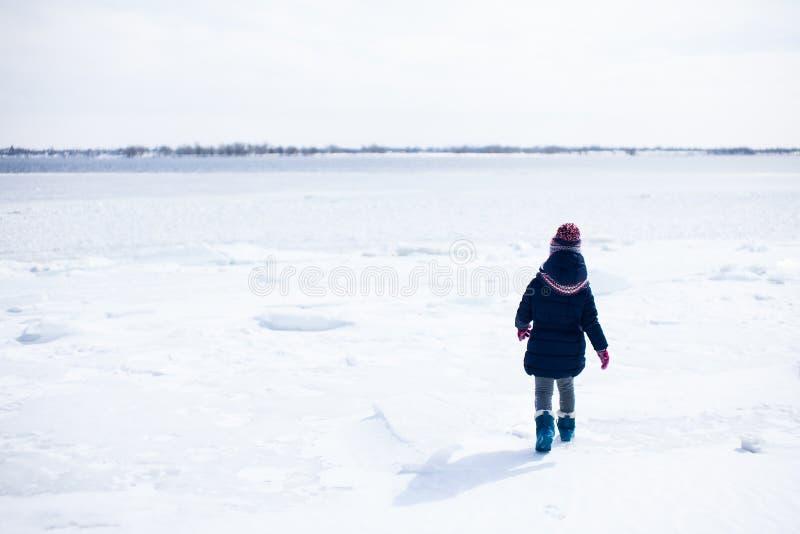 Małej dziewczynki odprowadzenie w śniegu w ciepłych płótnach zdjęcie royalty free