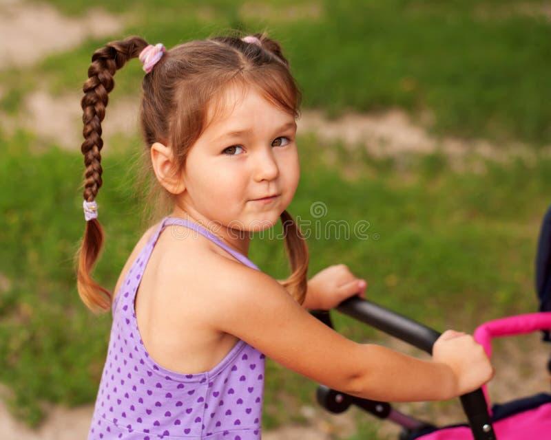 Małej dziewczynki odprowadzenie z zabawkarskim spacerowiczem. fotografia stock