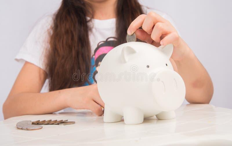 Małej dziewczynki oszczędzania pieniądze w białym prosiątko banku obraz royalty free