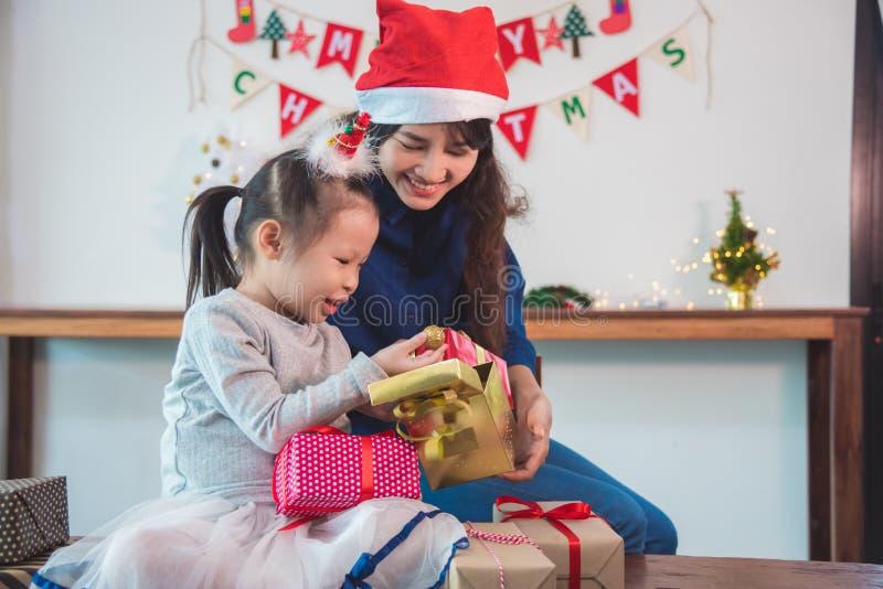 Małej dziewczynki otwarcia święto bożęgo narodzenia prezent z jej matką fotografia royalty free