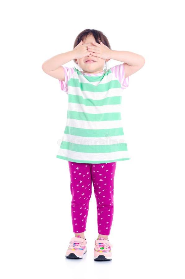 Małej dziewczynki pokrywa ona oczy rękami nad bielem zdjęcie stock